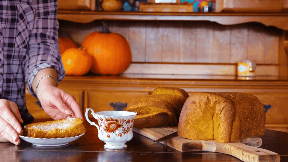 vegan pumpkin seed bread sliced on the table with pumpkins in the background.