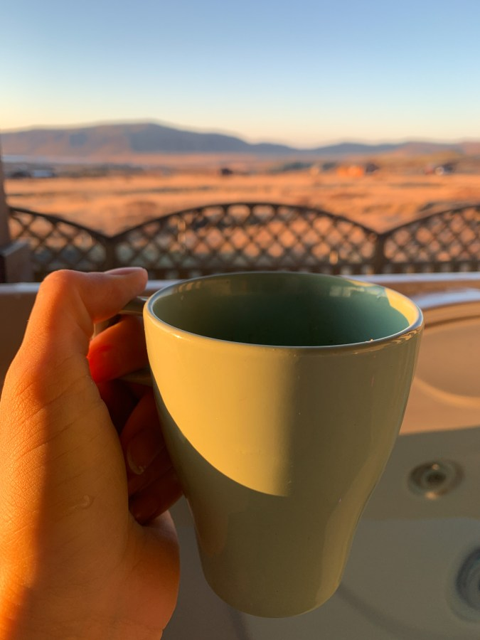 holding a cup of coffee outdoors