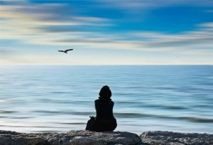 A woman sits in meditation as she looks out at a blue ocean. She may be exploring her deeper nature by asking herself 'Who am I?'