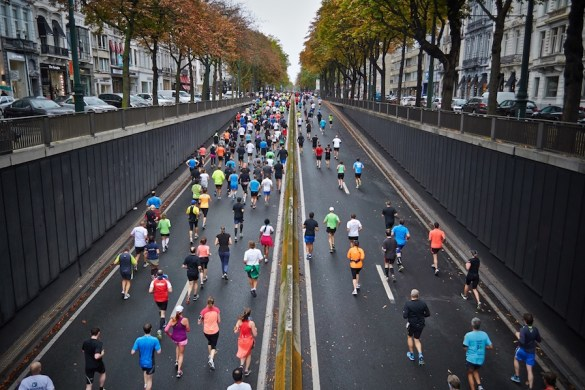 A man takes a photo from a bridge and marathon racers run underneath him. Action is the king of achievement.