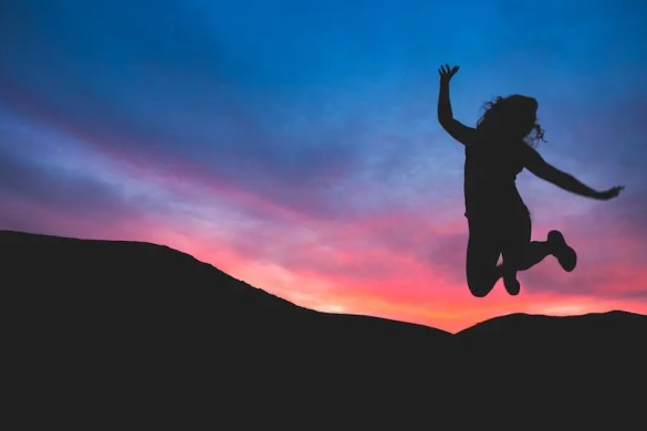 A women jumps in the air as the sunsets in the background. She is accepting her situation as it is.