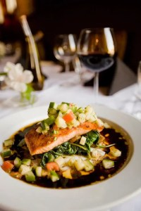 A piece of wholesome salmon is shown on a bed of vegetables.