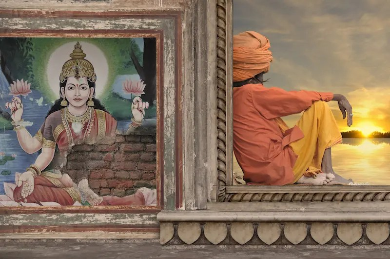 A man sits with his back against a wall that has Indian art and a picture of a God. Hinduism 101