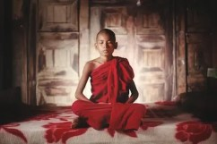 A young buddhist monk sits in a lotus position as he practices meditation.