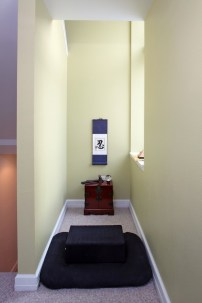 A meditation room is shown in a nook of a house