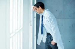 A medical student looks out a window anxiously. The reality of the mind-body connection can help treat the negative physical symptoms of anxiety.