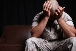 A soldier has his hands in his head as he deals with the stress of everyday military life. The mind-body connection can help us treat military personal in natural ways.