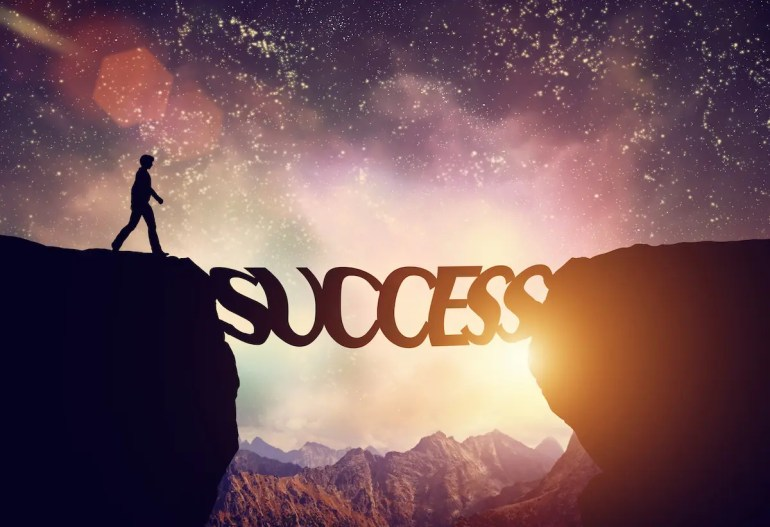 A man walks across a bridge that says success. By unifying your personal development approach, success is nearly guaranteed.