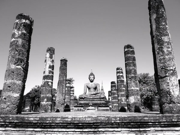 A statue of the Buddha shown with pillars in black and white.