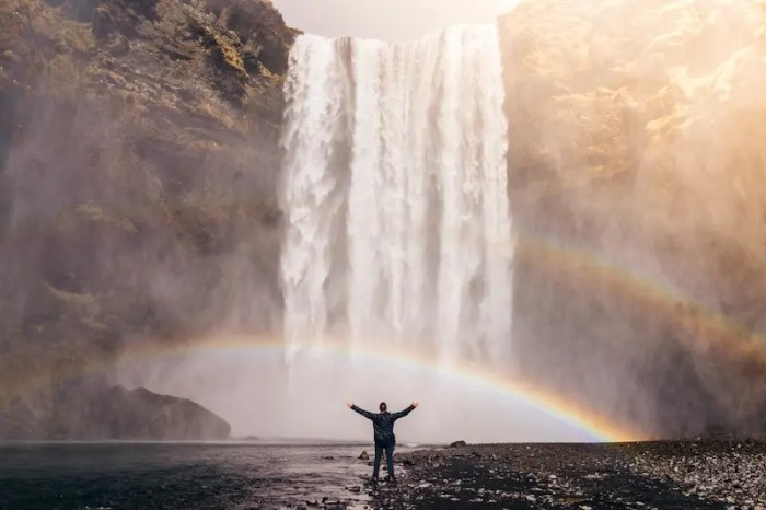 "A man is pictured standing at a waterfall with his arms in the air. By asking yourself ""what am I grateful for?"" you can certainly find happiness in countless ways."