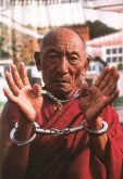 Palden Gyatso is shown with shackles on his wrists and arms. He was a Chinese prisoner for over 30 years.