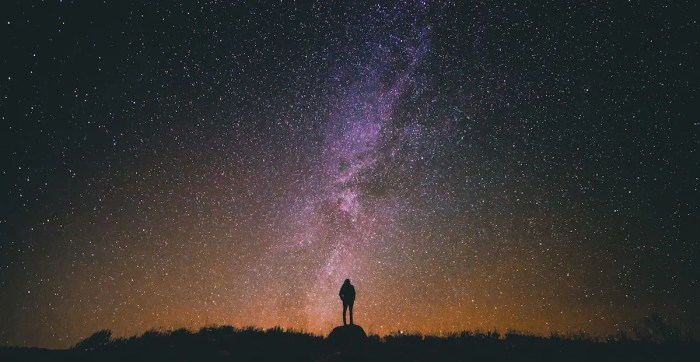 A man is shown looking up at a star filled sky. This represents how an individual's true self is beyond their ego.