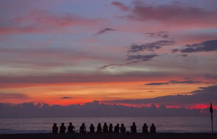 A sunset is shown with 13 friends watching it on a beach. Instead of chasing millions, you should chase meaningful experiences and relationships.