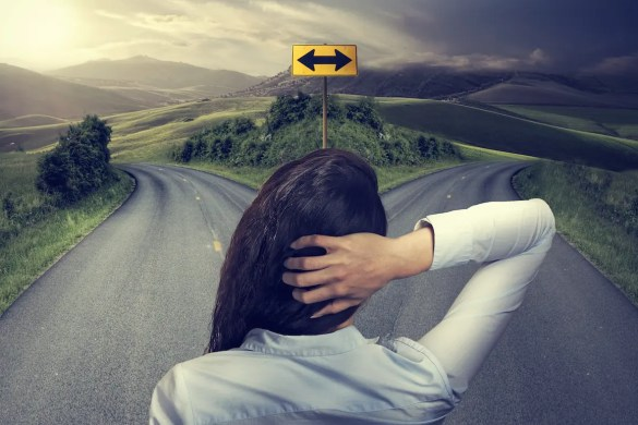 A woman looks down a split road with her hand on the back of her head. The sky is cloudy on one of the streets and sunny on the others. The picture serves as a reminder that while decision-making may seem easy, it is often challenging.