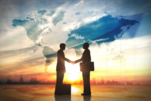 The Triple Bottom Line, a new way to do business. The picture shows two men shaking hands with a world map in the backdrop.