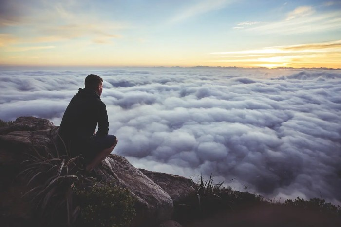 A man kneels down on a high mountain and looks out to see the clouds below him. This image represents the equation of unbreakable determination.