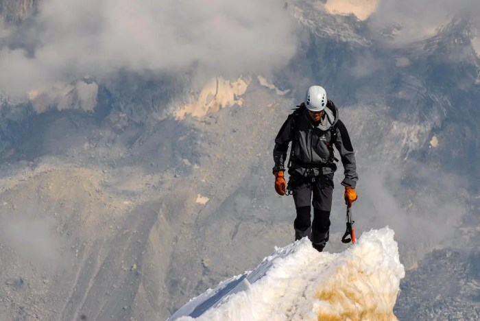 A high altitude mountain climber is shower with an ice pick in hand climbing a steep sheet of ice. His determination is apparent.
