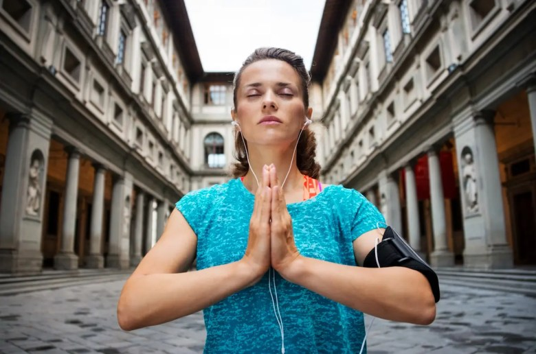 Young fitness woman is pictured meditating with headphones on in with a urban backdrop. This picture is meant to show how the Headspace app can help users find inner peace regardless of where they are.