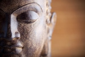 A statue of half of the Buddha's face is shown. This picture represents the 3 marks of existence and the truth of non-self.