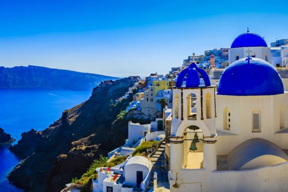 A Greek island is shown with white buildings and blue roofs looking out over the blue mediterranean. This picture represents the Blue Zones.