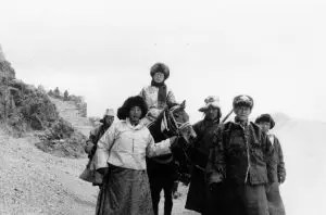 A picture is shown of the Dalai Lama on horseback with other members of his party making their way into exile towards Dharmasala.