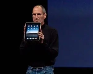 Steve Jobs is shown giving a speech while holding one of the iPads that he revolutionized. Jobs is the fourth of the famous failures that this article looks at.