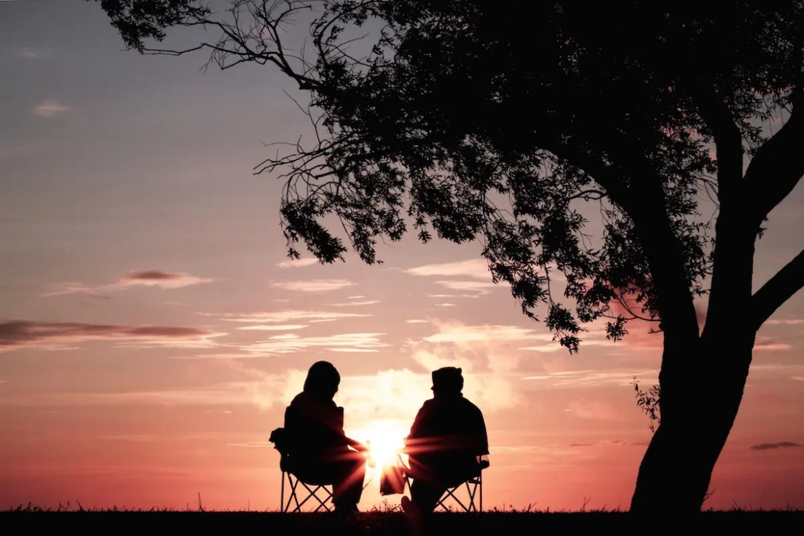 Two people are shown sitting in lawn chairs on a hill as the sunsets in the background. They are facing each other and talking in conversation. This photo represents the idea that empathy can help us connect with others.