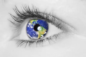 An image is shown of a woman's eye with a picture of the world superimposed on her eyeball. This image represents the idea that we have to search for ways to help the greater good.