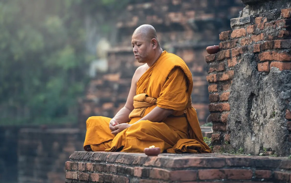 A Buddhist monk is shown meditating outside of a temple. He assuredly is using a Buddhist meditation techniques.
