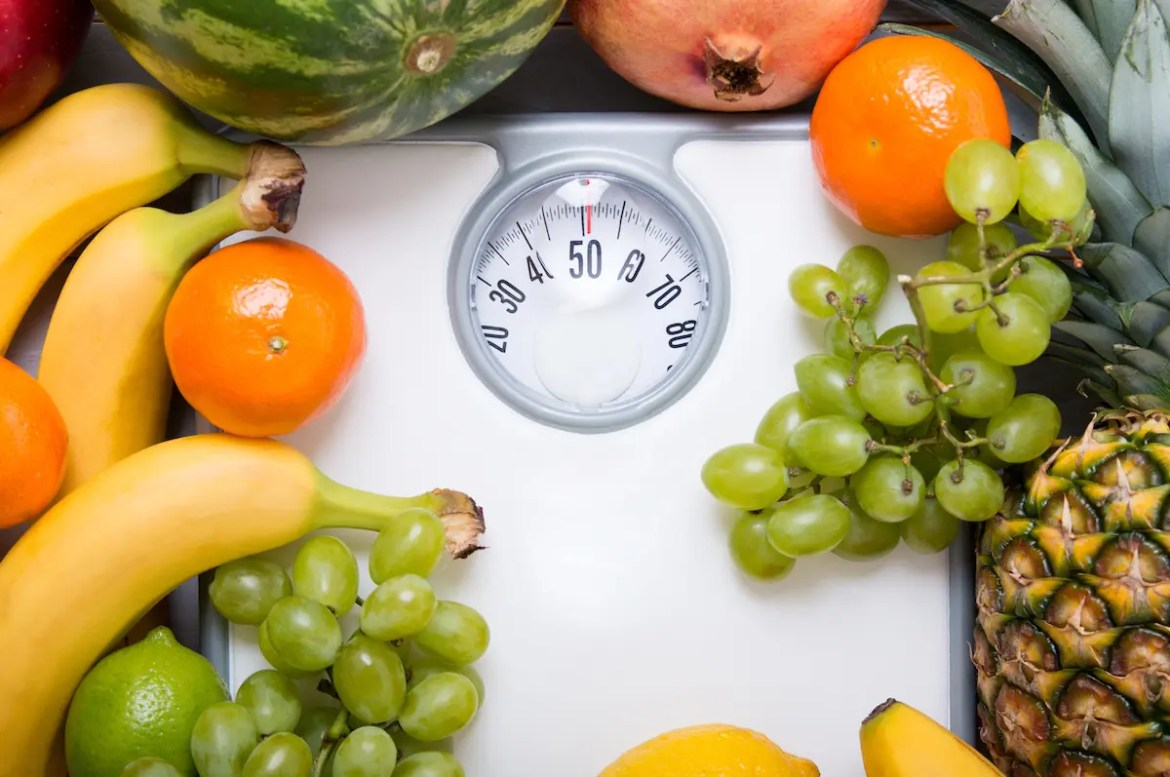 A variety of different fruits are pictured sitting on the outer edges of a white scale. This picture serves as the featured image of the article titled The Only True Way to Lose Weight.