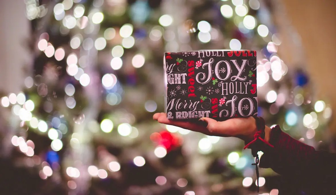 A woman's hand is shown holding a Christmas present wrapped in decorative paper that says words like joy & holly. This image serves as the featured image of Balanced Achievement's article 'Society's Greatest Parenting Mistake'.