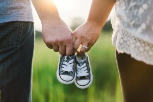 The hands of two parents are shown holding the shoes of their child together in unity.