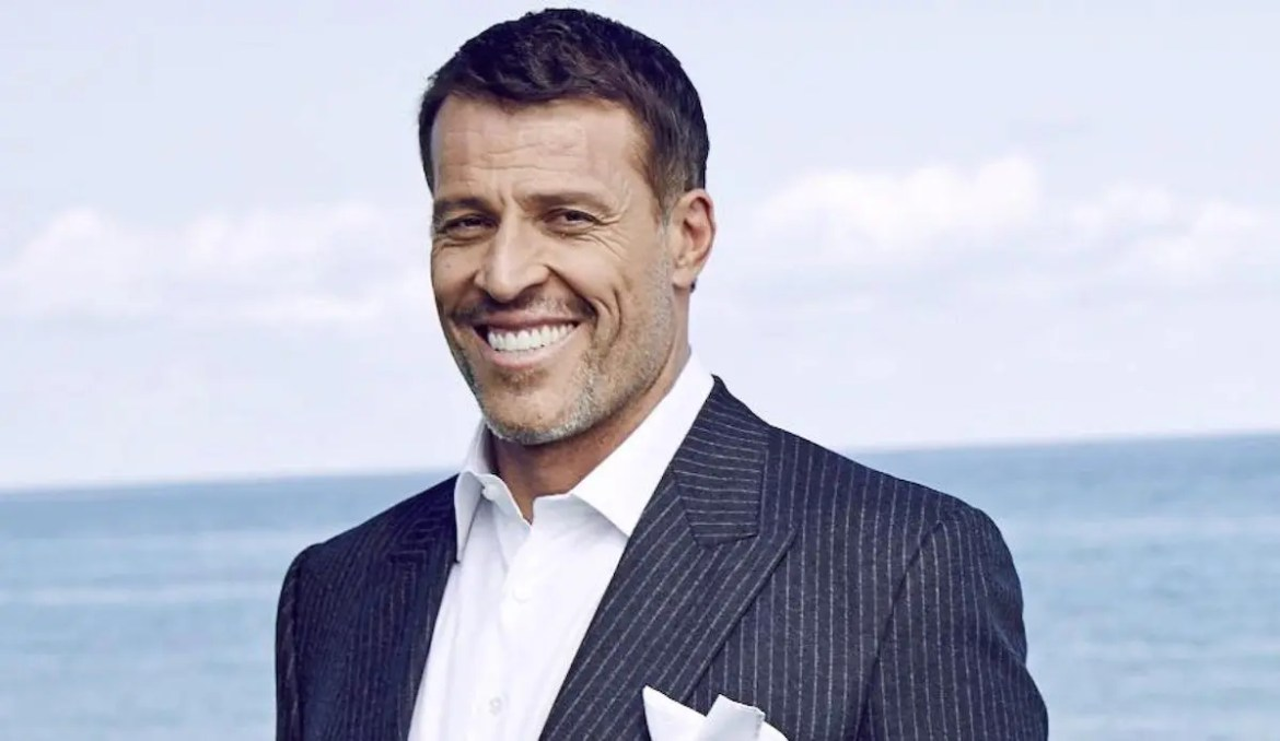 An image shows Tony Robbins smiling in a suite while on the beach.