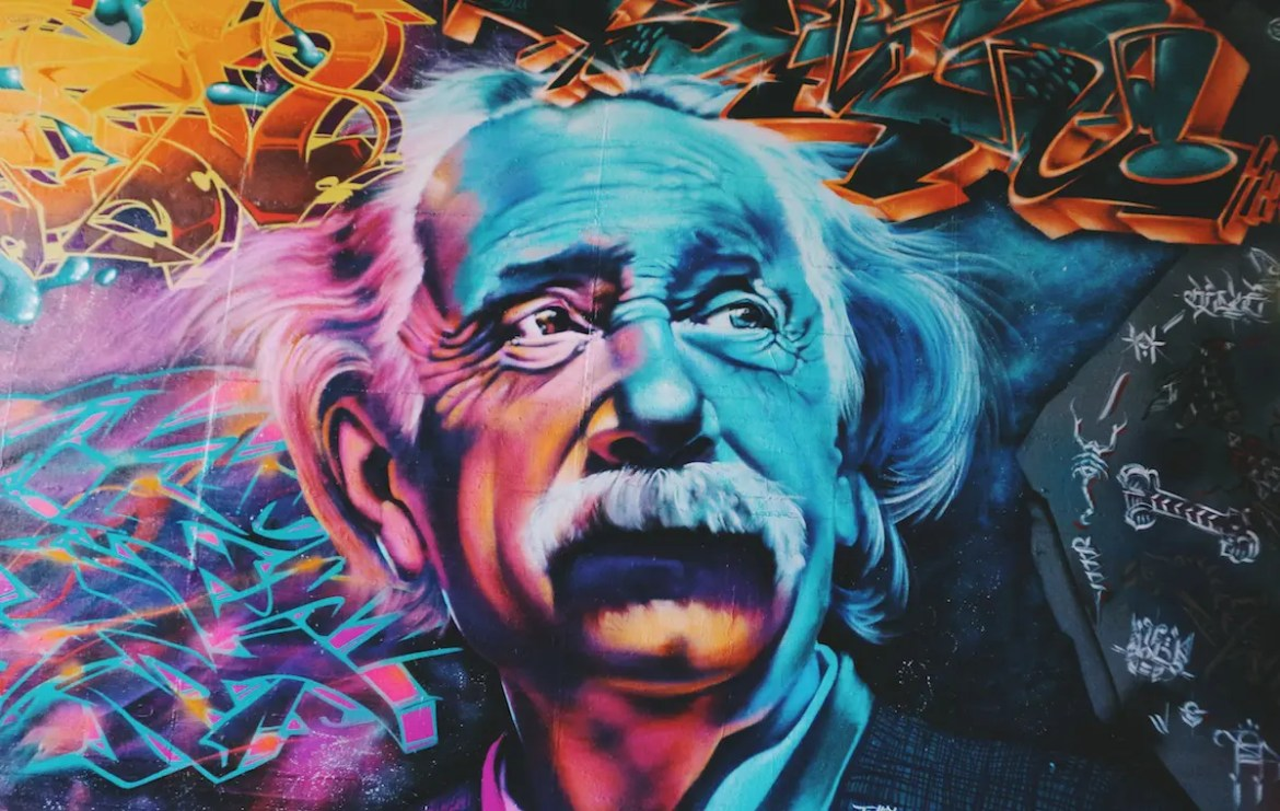 A graffiti portrait is shown of Albert Einstein colored in a variety of bright colors. This image serves as the featured image of the article Albert Einstein on God, Religion & Gandhi.
