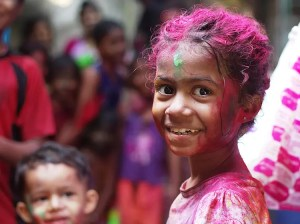 A young Hindu girl is pictured with washable and colorful paint on her clothes, faces, and in her hair. She just finished celebrating Holi.