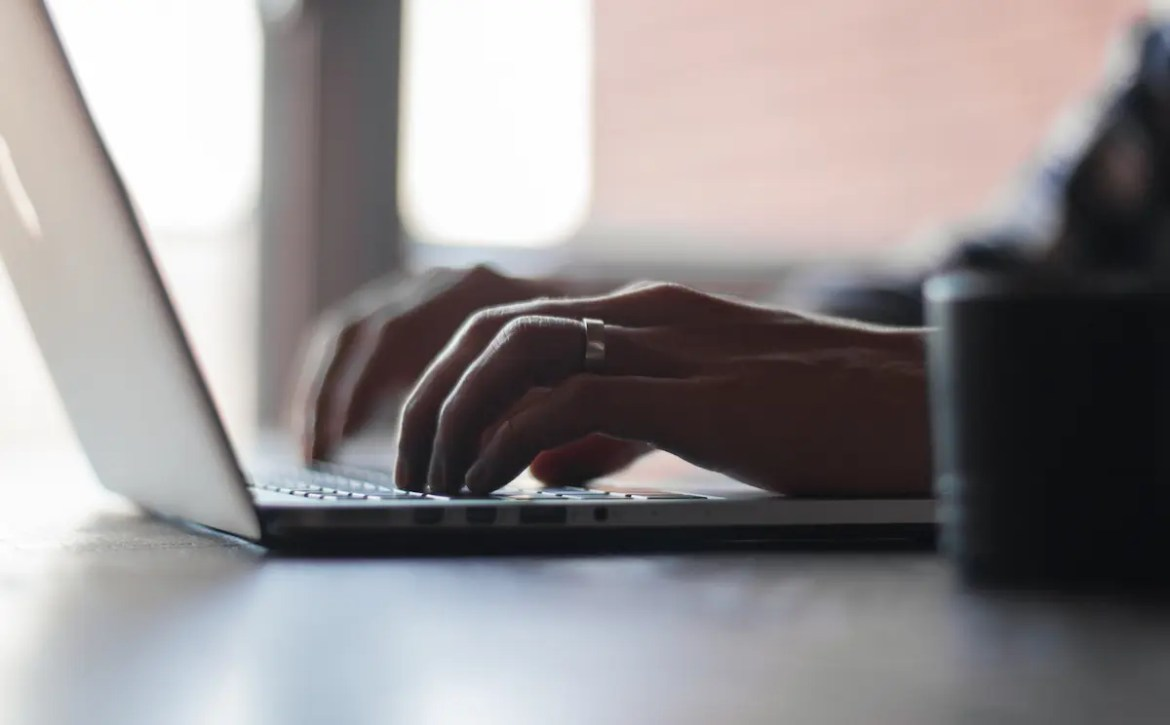 An image shows a man's hands working on his computer. This picture serves as the featured image of Balanced Achievement's Your Brain is a Computer, You are the User Article.