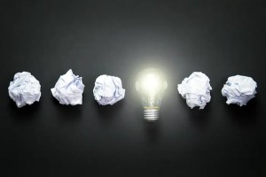 A computer generated image shows a light bulb in a row with crumpled paper and represents the idea of flexible focus being vital for achievement.