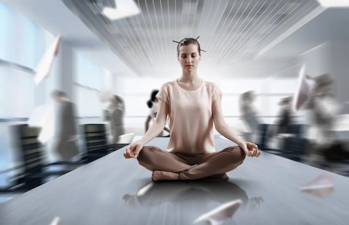 A young woman is see peacefully meditating on an office table as papers and people move hectically around her. This image represents one of the many benefits of meditation which is that it helps us professionally.