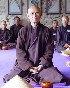 Thich Nhat Hanh is shown sitting in a traditional meditation posture.
