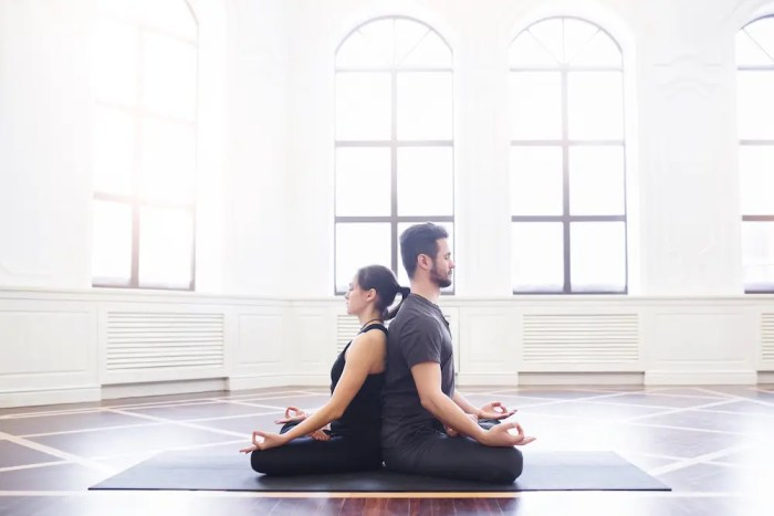 A young couple is shown meditating together, sitting back to back on a yoga mat, in a bright room with windows in the background. One of the benefits of meditation is that it improves relationships.