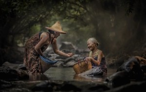 An image shows two Asian women working next to each other in a stream. One of the ladies is handing the other one something she found in the stream and both of them are smiling.