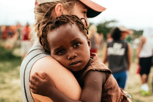 An image shows an American volunteer working in Africa and holding an African baby who's looking into the camera. This picture serves as the featured image of Balanced Achievement's article on Moral Elevation