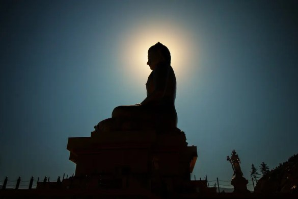 An image shows a statue of the Buddha with the sun directly behind his head as if it is giving him a bright halo. This picture serves as the featured image of Balanced Achievement's article examining The Buddha as a psychologist.