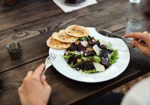 An image shows a woman's hands with a fork and a knife as she is about to eat a healthy salad. This image represents the idea that mindful eating is beneficial for our health.