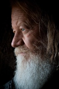 An image shows an older wrinkled man with a white beard and long hair casually looking out of a window. This image illuminates how many individuals compile numerous regrets throughout their lives which shows why asking 'Will I regret this in the future?' is so important.