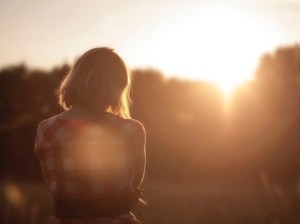The back of a woman is shown as the sun shines down on her. Her arms or crossed and she is looking down in contemplation. This image represents the idea that self-acceptance and love is vital for our happiness.