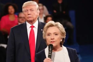 An image is shown from a 2016 Presidential Debate where Hillary Clinton is speaking in the foreground and Donald Trump is glaring at her with a nasty look on his face in the background.