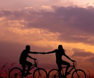 An image shows the silhouettes of a man and a woman riding on bikes. They both have one hand on their bikes and are reaching out holding hands with the others. She is riding in front of him and looking back. A beautiful sunset gives the background sky a nice color. This image represents the fact that one of our most important core beliefs is if we feel lovable.