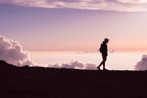 An image shows the silhouette of a man high in the mountains above the clouds walking along a mountain edge with a purple sky in the background. This image serves as the featured image of Balanced Achievement article on winning the game of real.