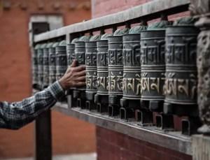 An image shows a man's hand as he spins a row of Buddha Dharma Wheels that represent the Buddha's Teachings.